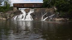 Waterfall under covered bridge Stock Footage