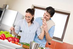 Smiling couple cook in modern kitchen Stock Photos