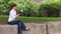 Caucasian woman in a park reading book Stock Footage