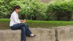 Caucasian woman in a park with tablet Stock Footage