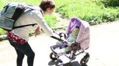 Mother walking with baby with in the stroller in park - stock footage