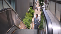 Japanese young businesswoman riding escalator, Tokyo, Japan - stock footage