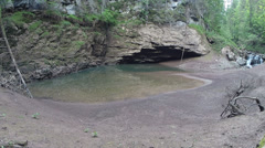 A river entering in a cave Stock Footage