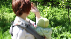 Mother walking with baby in park and rips dandelion - stock footage