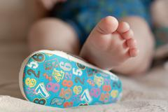 Stock Photo of a close-up of tiny baby feet. closeup of adorable title baby shoes