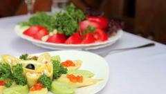 Dish of pancakes with caviar.Vegetables in the background. Stock Footage