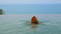 Curly Young Woman Swimming in Endless Luxurious Pool Stock Footage