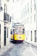yellow ancient tram on streets of lisbon, portugal - stock photo