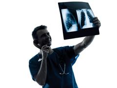 Doctor surgeon radiologist on the phone examining lung torso  x-ray image sil Stock Photos