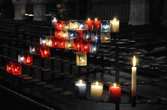 Many religious candles on a black support - stock photo
