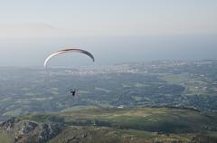 Paraglider man above Atlantic coast - stock photo