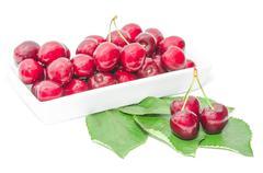 dark vinous cherry berries served in square white dish - stock photo