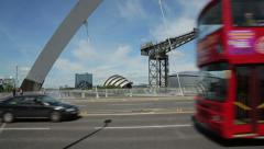 Joggers and tour bus cross the clyde arc bridge, glasgow, scotland Stock Footage