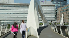 People walk across squiggly bridge over river clyde, glasgow, scotland Stock Footage