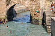 Stock Photo of essaouira - september 29: children take a bath in the canal. essaouira, moroc