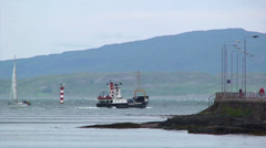 Boat sails away from Oban port into the loch Stock Footage