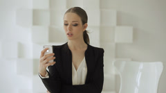 Beautiful young woman standing in trendy office and using her smartphone. Stock Footage
