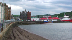 Beach in Oban city, with North Pier of the port in background Stock Footage