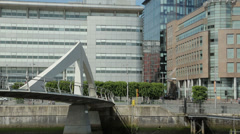 People cross the squiggly bridge over river clyde, glasgow, scotland Stock Footage