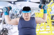 Stock Photo of fat man exercise in fitness center