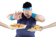 Fat man rejecting junk food Stock Photos