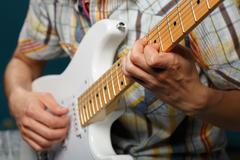 Play on guitar, selective focus on part of strings Stock Photos