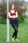 Brunette leaning against street pole Stock Photos