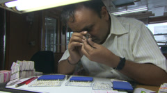 Man examines diamonds using magnifier - stock footage