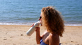 Young Woman Drinking Milk and Pouring It Over Her Curly Hair on the Beach. Funny Footage