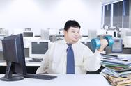 Stock Photo of obesity businessman working while workout