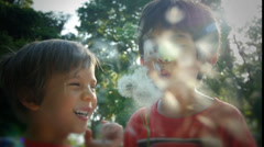 Two Children blowing Dandelions and laughing in slow motion Stock Footage