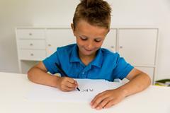 boy writing the abc alphabet - stock photo