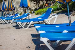 Deck chairs over the sand in a idyllic beach in ibiza, balearic islands, spai Stock Photos