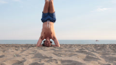 Man practicing sirsasana yoga pose Stock Footage