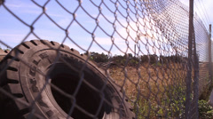 Tractor tire and mill through fence - stock footage