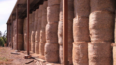 Hay bales stacked up in shed Stock Footage