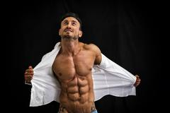 male bodybuilder taking off his shirt revealing muscular torso - stock photo