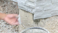 Stock Video Footage of worker install stone wall surface with cement for house
