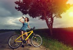 beautiful sports girl with bike drinking water from a bottle. - stock photo
