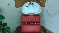 Chair and head hair wash basin sink at barber hairdresser salon Stock Footage
