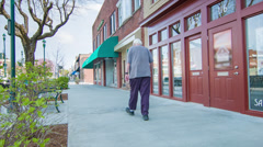 Retired Senior Citizen Walking Down Main Street USA Stock Footage