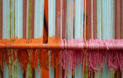 Wool weavings of many colors in the old textile loom Stock Photos