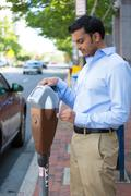 closeup portrait, young man putting coins in parking meter outside to prevent - stock photo