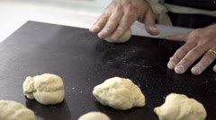 Man kneading bread dough in a black countertop - stock footage