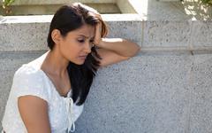 Closeup portrait, dull upset sad young woman in white dress sitting on bench Kuvituskuvat