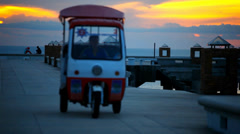 Golf car rides on the pier at sunset and a couple love sitting watching Sunset. Stock Footage