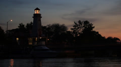 Port Credit Lighthouse in Evening with traffic on Lakeshore Boulevard Stock Footage