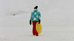 Young girls with sleds, sledges or toboggans climb a hill Stock Footage