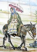 azulejo girl with umbrella riding a donkey - stock photo