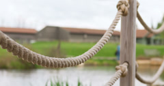 Rope railing and post by pond 4k Stock Footage